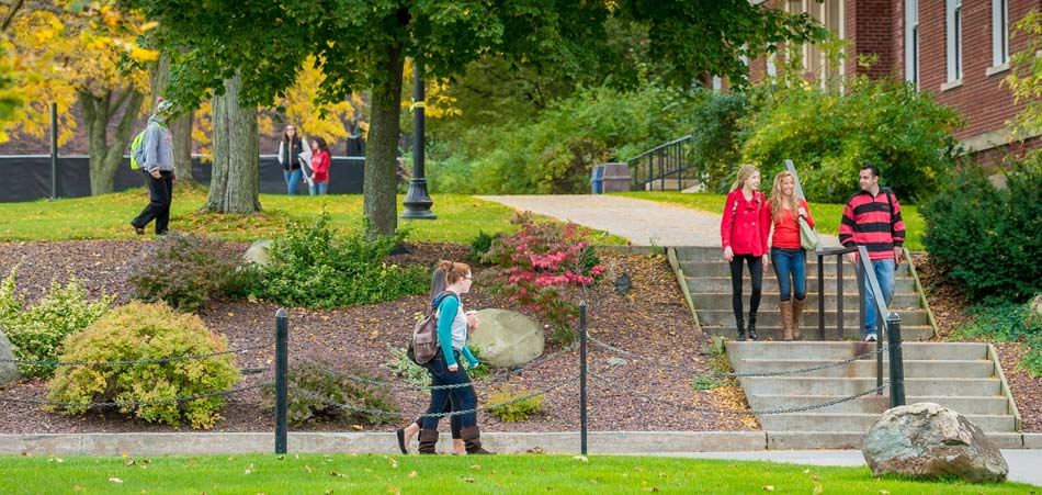 Students walking on campus by landscaping