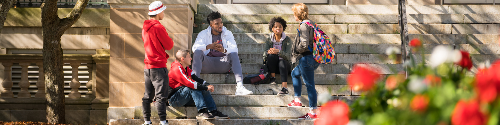 Students talking and sitting on the steps outside of Old Main