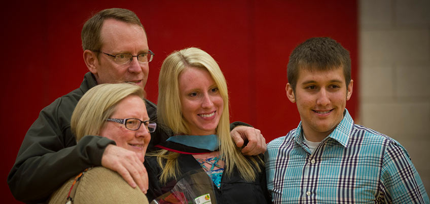Graduate and family smile for a picture