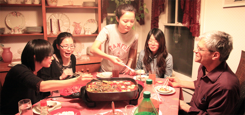 International Students Sharing a Traditional Dinner with Host Family