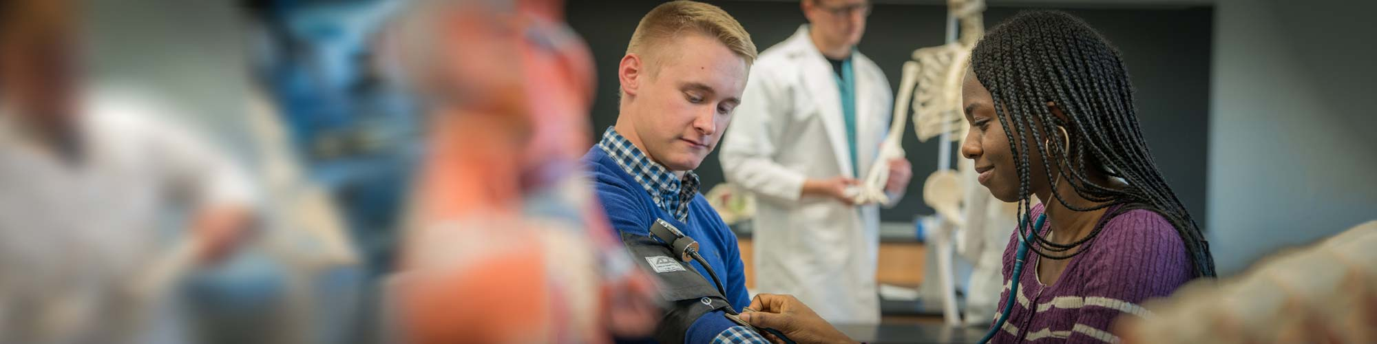 Pre-med Club students practice blood pressure readings on each other