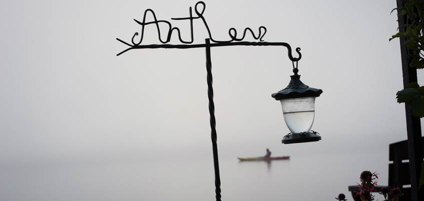 Antler's sign and hummingbird feeder and kayaker on a foggy morning