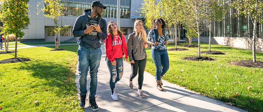 Laughing students walk together outside of the Student Life Center