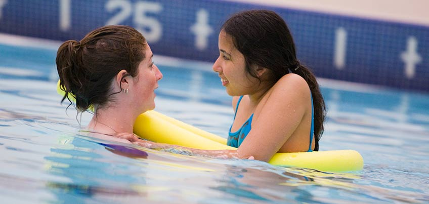 Adaptive Physical Education student helps a young girl learn to swim