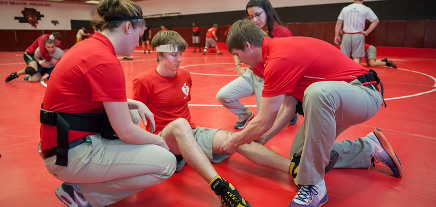 Athletic training students working with a Cortland wrestler