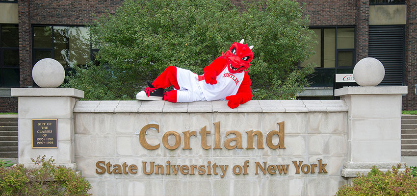 Blaze sitting on the SUNY Cortland sign