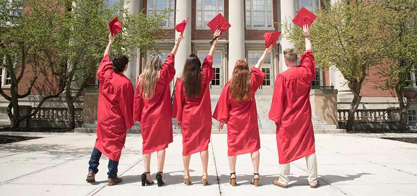 Five graduates in red regalia stand facing Old Main Building, hold their caps high above their heads..