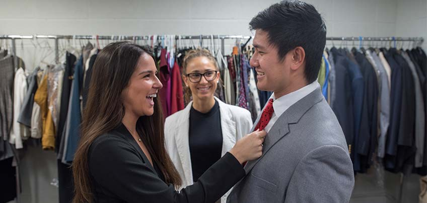 A student trying on a suit in the Clothing Closet