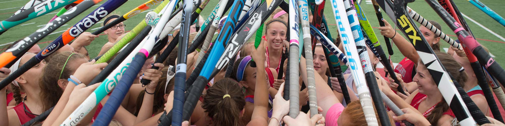 sport camp participants hold up their field hockey sticks