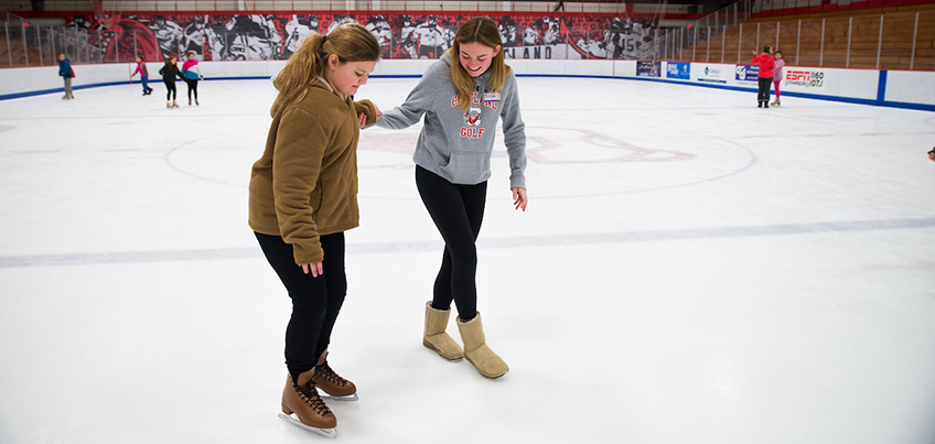 Student helping a local youth skate at Girls Night Out