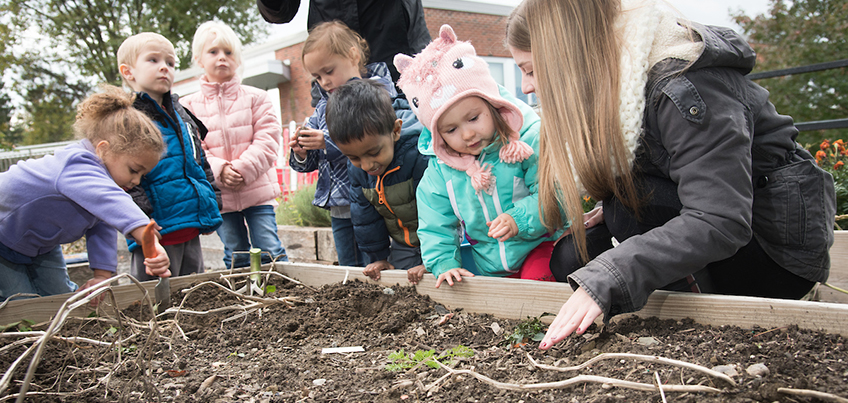 Young children working in campus garden with a student