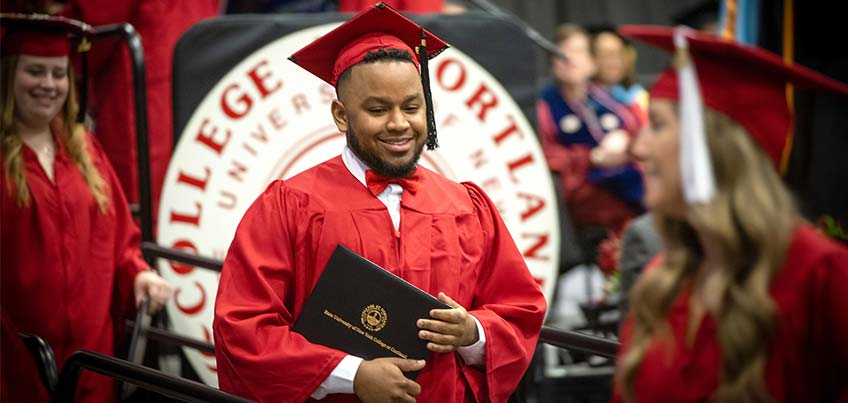 Student receives his diploma at Commencement