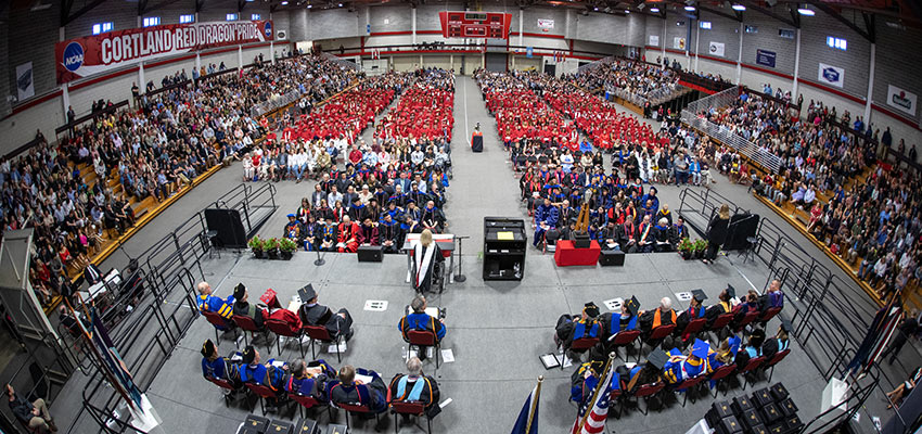 Wide-angle view of the commencement ceremony, with faculty/staff in formal regalia and students in red, viewed from above center stage