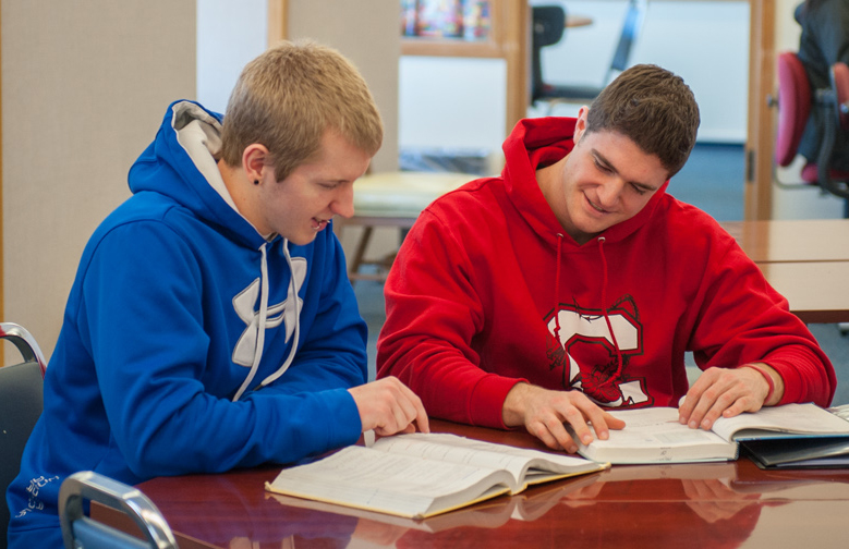 Two students studying together at a table in ASAP