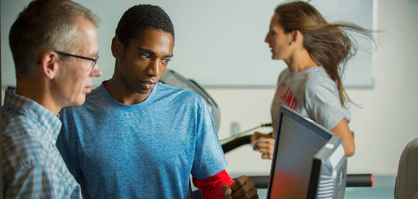 Student and professor evaluating another student's treadmill activity