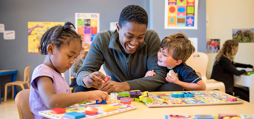 A SUNY Cortland student helps two children with wooden puzzles in the Child Care Center