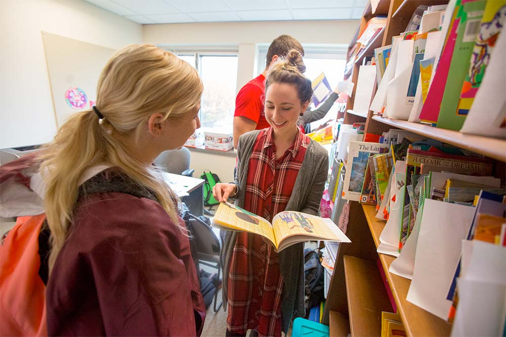 Literacy graduate students read books together