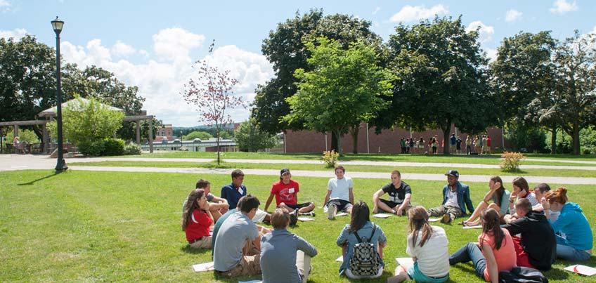 Orientation group sitting on the lawn outside of Sperry Center