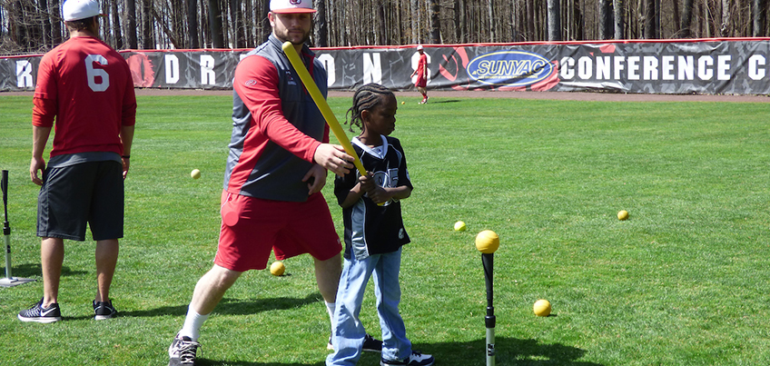 Baseball student-athlete working with a child at a youth clinic
