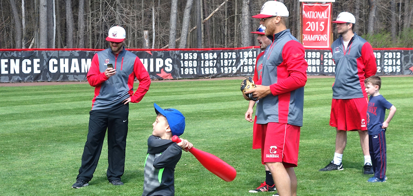 Local child swinging a bat with Cortland baseball players looking on