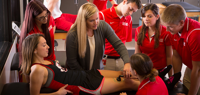 Athletic training students working with professor