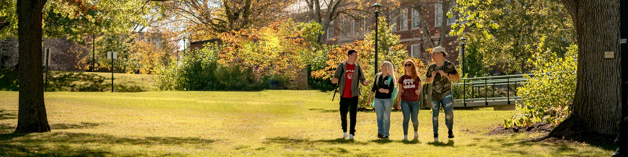Students walking in front of Moffett Center on a fall day