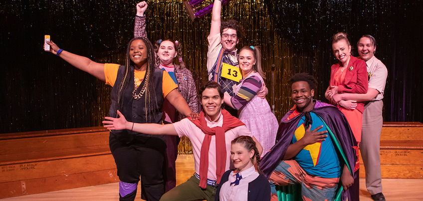 Spelling Bee musical cast smiles on stage