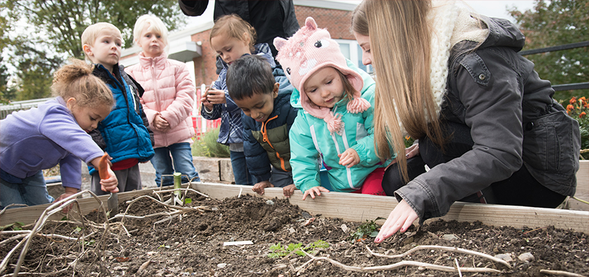 Cortland students help preschool students plant flowers in a raised bed