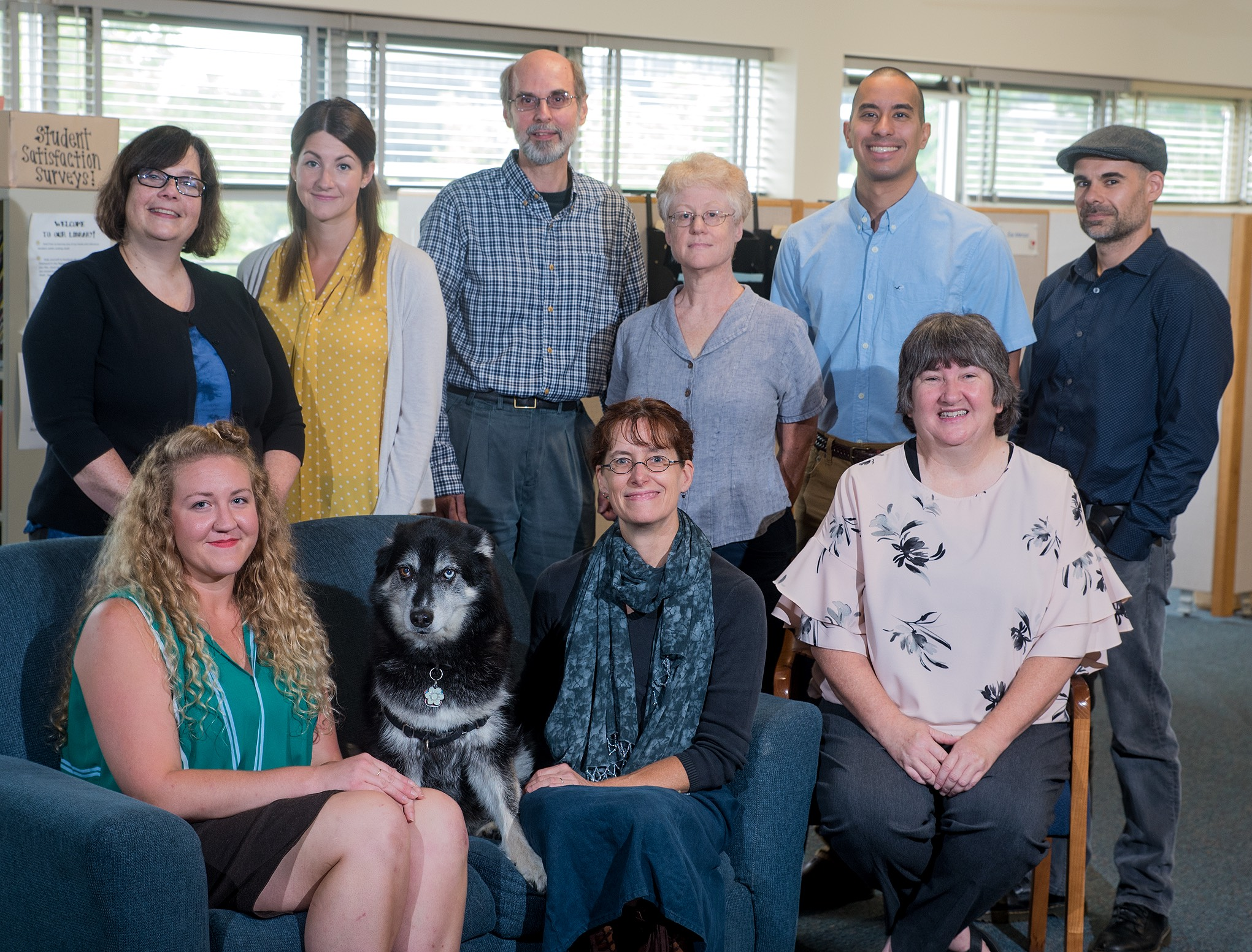 Group photo of TLC staff positioned around the office couch. Top row (left to right): Esa, Christina, Mark, Jeanine, Chris, and Ray. Bottom row (left to right): Amy, Sona the dog, Jen, and Teresa.