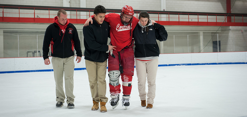 Athletic training students help carry a hockey player off the ice
