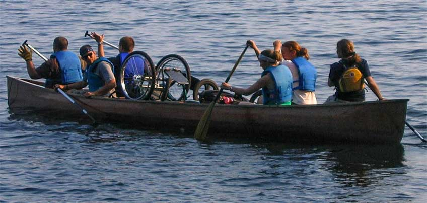 students and wheelchair in canoe