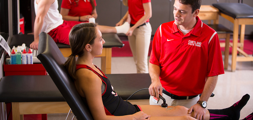 Athletic training student treats a leg injury