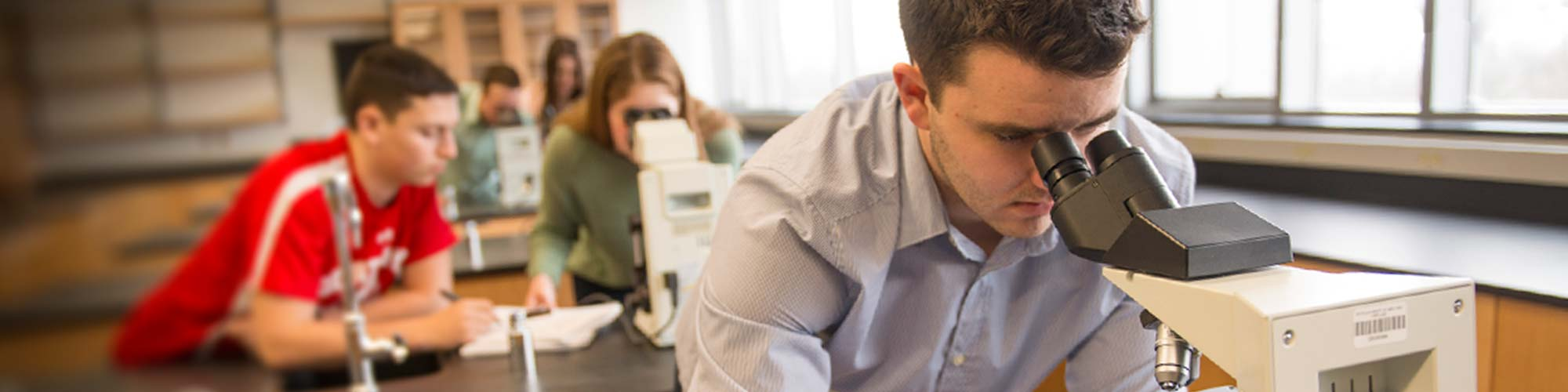 Biology majors peering through microscopes