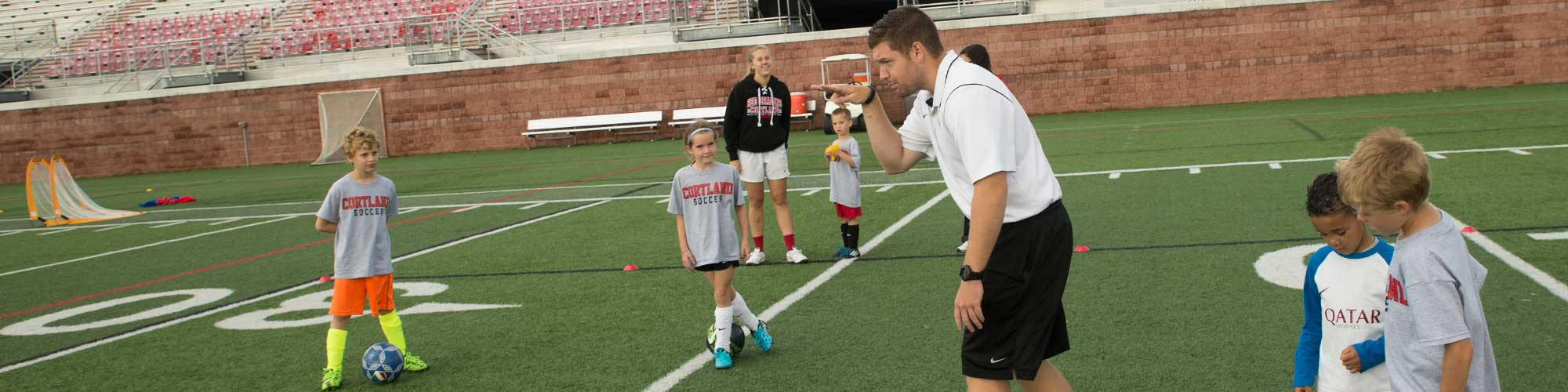 Soccer camp coach leads young campers in drills.