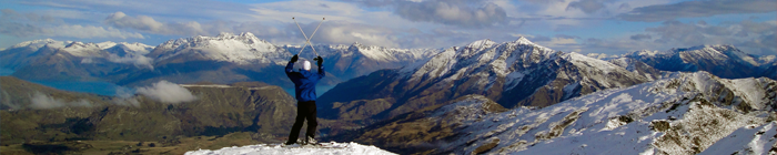 Interested in Studying Abroad? Come to a Study Abroad 101  Info-session! Student looking out over snowy mountains, lifting his ski poles above his head.