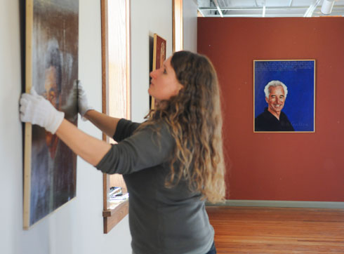 "Jaroslava Prihodova, the Dowd Gallery's manager, preps for the ""Americans Who Tell the Truth"" exhibition. The portrait of Bill Griffen can be seen in the background."