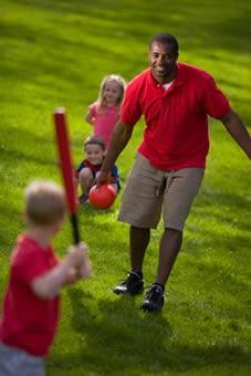 A man playing softball with young children