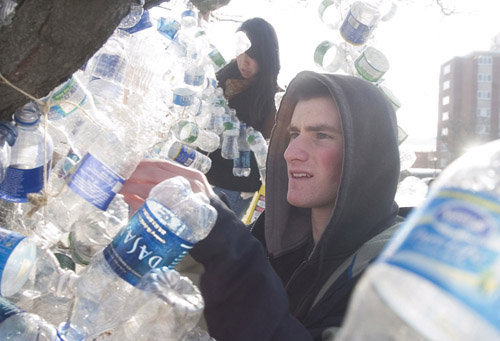 SUNY Cortland senior Mark Morrell strings collected plastic bottles