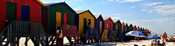 Apply Now link - Colorful houses sitting side-by-side on a beach in Africa
