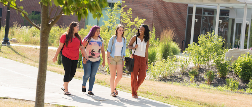 Students chat as they walk together outside on campus.