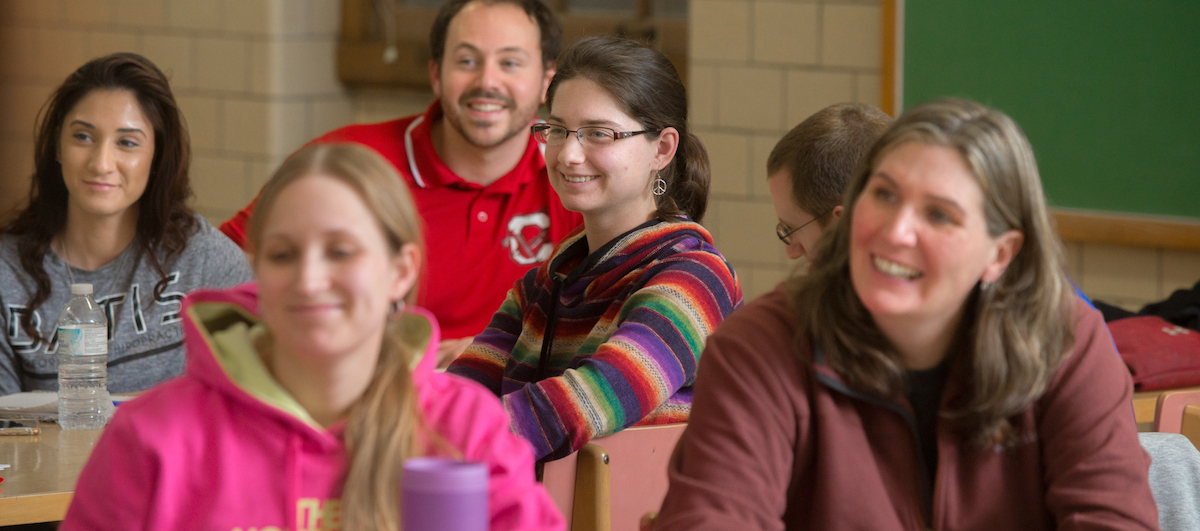 Students in a classroom looking attentatively ahead and smiling
