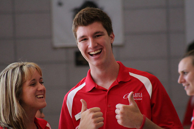 Orientation assistants laugh together, as one gives two thumbs up.