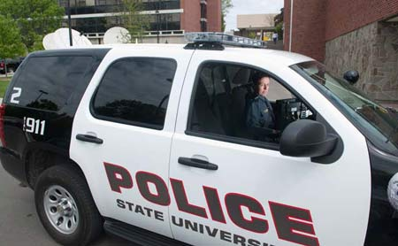 A SUNY Cortland police office inside a police vehicle.
