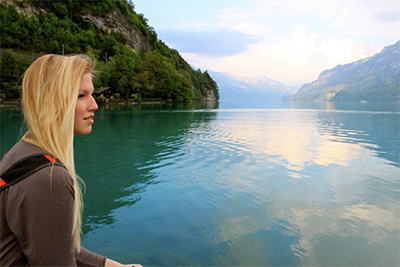 Study Abroad Page Link - Study Abroad participant looking off onto green mountains and calm lake