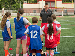 coach instructing youth soccer players
