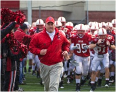A coach leads the Cortland football team onto the field.