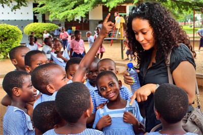 Faculty Page link - Student chatting with school-children in Ghana