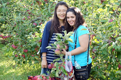 International Students and Services Page link - Two international students going apple-picking