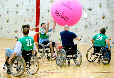 Group in wheelchairs playing with giant ball