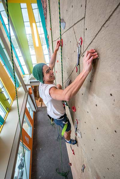 A climber ascends the climbing wall in the Student Life Center.